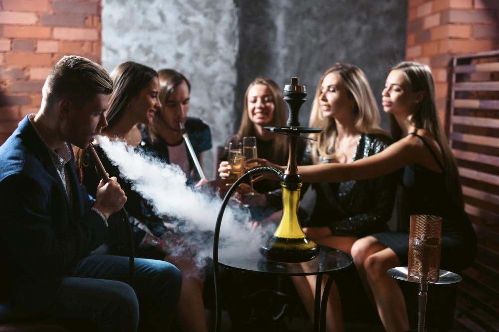 Grupa znajomych palących żółtą fajkę wodną